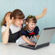 Girl and mother are playing with laptop — Stock Photo