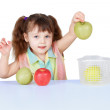 Little girl playing with green apples - Foto Stock