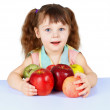 Little girl playing with apples sitting at table - Stock Photo