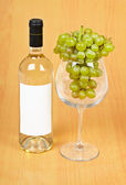 A bottle of wine, a large glass and grapes — Stock Photo