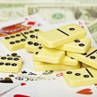 Handful of dominoes on cards and money — Stock Photo