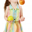 Little funny girl juggles fruit - Stock Photo