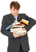 Man - student hold heap of books and textbooks — Stockfoto