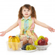 Little girl with big heap of different fruits — Stock Photo