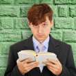Royalty-Free Stock Photo: Person reads book on background of green wall