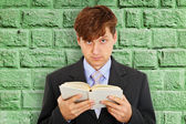 Person reads book on background of green wall — Stock Photo