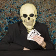 Horrible cardsharper in mask - skull - Stock Photo