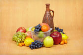 Still life of fruit and ceramic bottle — Stock Photo