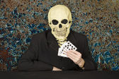 Horrible cardsharper in mask - skull — Stock Photo