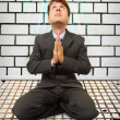 Comic businessman on knees praying — Stock Photo