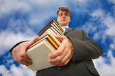 Man with big stack of books against sky — Stock Photo