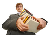 Young man with pile of books in hands — Stock Photo
