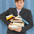Stock Photo: Funny guy with an armful of textbooks