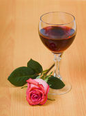 Glass of red wine and rose — Stock Photo
