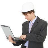 Builder works with laptop holding it on hands — Stock fotografie