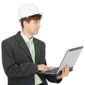 Smiling engineer in helmet with laptop in hands — Stock Photo