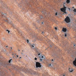 Iron sheet with rust and through holes - Stock Photo