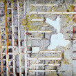 Wooden planks in damaged old concrete wall — Stock Photo