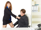 Woman to give a man thrashing in office — Stock Photo