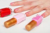 Women's hand and three bottles nail polish — Stock Photo