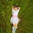 Stock Photo: Little girl lies in green grass