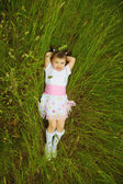 Little girl lies in green grass — Stock Photo