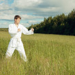 Man in kimono trains karate in open air — Stock Photo