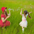 Mum and daughter starting up soap bubbles - Stockfoto