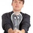 Young man with electric bulb in hands — Stock Photo
