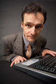 Amusing portrait of man on workplace at dark office — Stock Photo