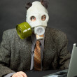 Amusing person has dressed gas mask and works with computer — Stok fotoğraf