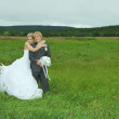 Royalty-Free Stock Photo: Bride and groom embrace on field