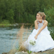 Sad bride sits on river bank — Stock Photo