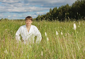 Young man in white kimono sits in grass — Stock Photo