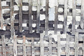 Old concrete wall is destroyed. Wooden skeleton is bared. — Stock Photo