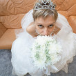 Stock Photo: Amusing bride sits on sofa with bouquet - top view