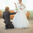 Stock Photo: Groom with bride funny pose in hall