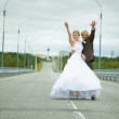 Newly married have fun on highway — Stock Photo