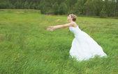 Bride hastens towards to groom on meadow — Stock Photo