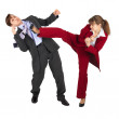 Young woman kicks man in business suit — Stockfoto