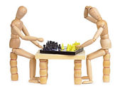 Two silly wooden men play chess — Stock Photo