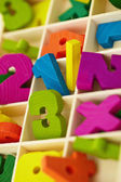 Wooden box with toy characters and numerals — Stock Photo