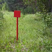 Placa de metal vermelha perto de floresta — Fotografia Stock