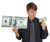 Businessman feels difference between large and small money — Stock Photo