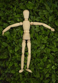 Toy wooden man on grass — Stock Photo