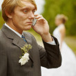 Stock Photo: Groom speaks by phone , forgotten about bride