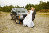 Newly married go to a honeymoon trip by car — Stock Photo
