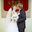 Newly married kiss under Russian arms — Stock Photo