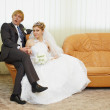 Royalty-Free Stock Photo: Amusing groom and bride sitting on armchair