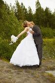 Groom passionately kisses bride — Stock Photo